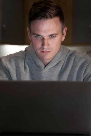 Suspicious Looking Man Using Laptop In Evening At Home Фото со стока