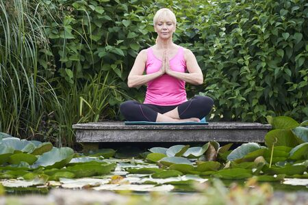 Mature Woman In Yoga Position On Wooden Jetty By Lake Фото со стока