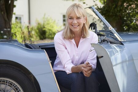 Portrait Of Proud Mature Woman Sitting In Restored Classic Sports Car Outdoors At Home Фото со стока