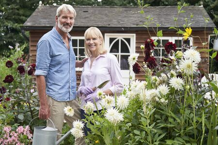 Portrait Of Mature Couple Working In Flower Beds In Garden At Home Фото со стока