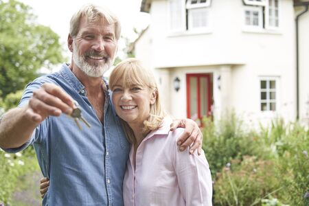 Portrait Of Mature Couple Standing In Garden In Front Of Dream Home In Countryside Holding Keys