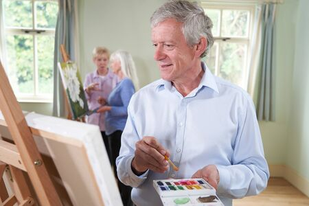 Senior Man Attending Painting Class With Teacher In Background