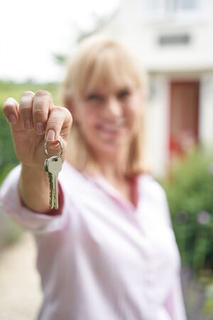 Portrait Of Mature Woman Standing In Garden In Front Of Dream Home In Countryside Holding Keys Фото со стока