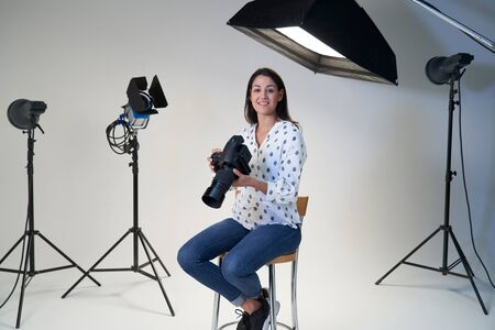 Portrait Of Female Photographer In Studio For Photo Shoot With Camera And Lighting Equipment Фото со стока