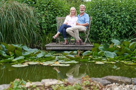 Portrait Of Mature Couple Celebrating With Champagne Sitting On Chairs On Wooden Jetty By Lake