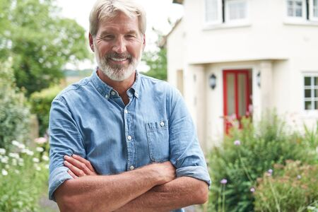 Portrait Of Mature Man Standing In Garden In Front Of Dream Home In Countryside