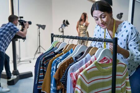 Stylist Choosing Clothes For Fashion To Wear On Photo Shoot In Studio