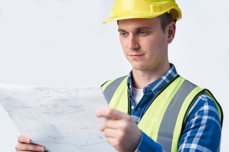 Studio Shot Of Builder Architect Looking At Plans Against White Background