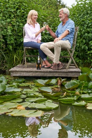 Mature Couple Celebrating With Champagne Sitting On Chairs On Wooden Jetty By Lake Фото со стока