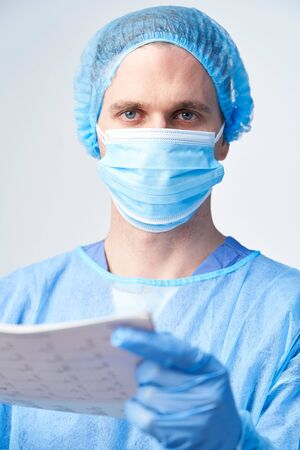Studio Portrait Of Male Surgeon Wearing Gown And Mask Holding Medical Print Out