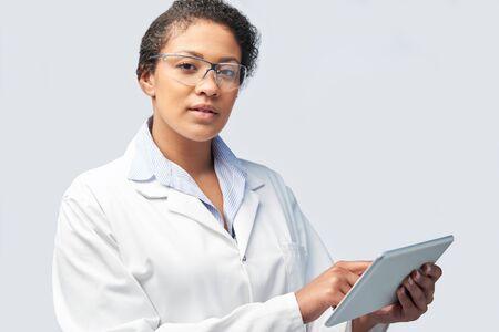 Studio Portrait Of Female Laboratory Technician Working With Digital Tablet
