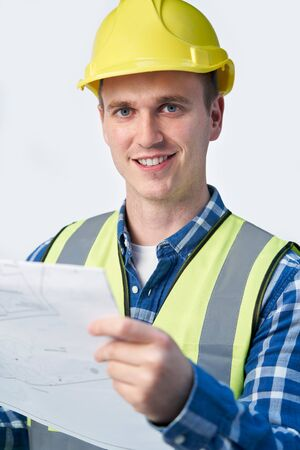 Studio Portrait Of Builder Architect Looking At Plans Against White Background Фото со стока