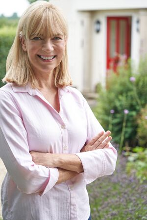 Portrait Of Mature Woman Standing In Garden In Front Of Dream Home In Countryside
