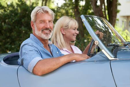 Portrait Of Mature Couple Enjoying Road Trip In Classic Open Top Sports Car Together