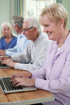 Senior Woman With Tutor In Computer Class Фото со стока