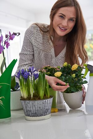 Portrait Of Young Woman Caring For Houseplants Indoors