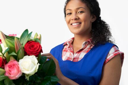 Portrait Of Female Florist Arranging Bouquet Of Lillies And Roses Against White Background Фото со стока