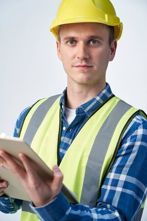 Studio Portrait Of Builder Architect Holding Clipboard Against White Background