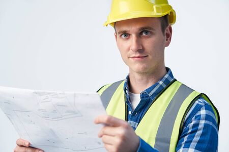 Studio Portrait Of Builder Architect Looking At Plans Against White Background Stock Photo