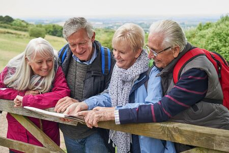 Group Of Senior Friends Hiking In Countryside Standing By Gate  Looking At Map