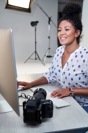 Female Photographer In Studio Reviewing Images From Photo Shoot On Computer
