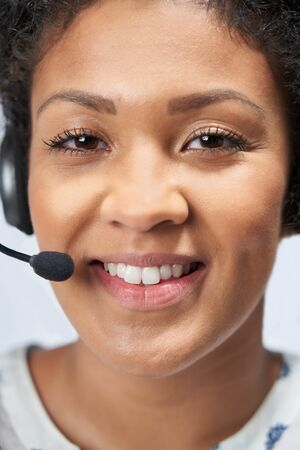 Portrait Of Businesswoman Wearing Telephone Headset In Customer Services Department
