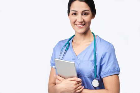 Studio Portrait Shot Of Female Nurse Wearing Scrubs Using Digital Tablet Stock Photo