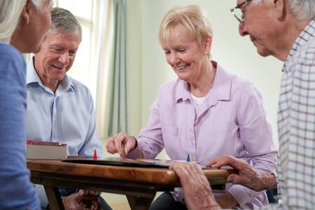 Group Of Retired Friends Playing Board Game At Social Club Stock Photo