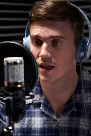Male Voice Over Artist In Recording Studio Talking Into Microphone Stock Photo