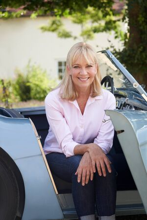 Portrait Of Proud Mature Woman Sitting In Restored Classic Sports Car Outdoors At Home Stock Photo