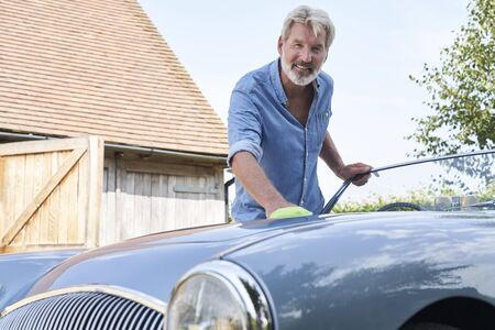 Porträt von reifer Mann Polieren restaurierten klassischen Sportwagen im Freien zu Hause
