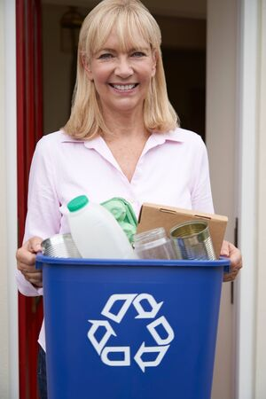 Portrait Of Mature Woman Holding Recycling Bin Of Reusable Waste Outside Front Door Stock Photo