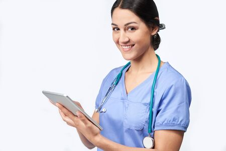 Portrait Of Studio Shot Of Female Nurse Wearing Scrubs Using Digital Tablet Stock Photo