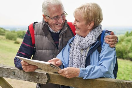 Retired Couple On Walking Holiday Resting On Gate With Map