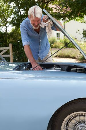 Mature Man Working On Engine Under Hood Of  Restored Classic Sports Car Outdoors At Home