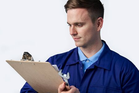 Male Engineer With Clipboard And Spanner Against White Background Stock Photo