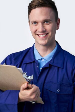 Studio Portrait Of Male Engineer With Clipboard And Spanner Against White Background Stock Photo