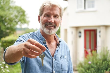 Portrait Of Mature Man Standing In Garden In Front Of Dream Home In Countryside Holding Keys
