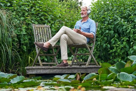 Mature Man Relaxing In Garden Listening To Music On Wireless Headphones On Jetty By Lake Stock Photo