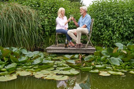 Mature Couple Celebrating With Champagne Sitting On Chairs On Wooden Jetty By Lake Stock Photo