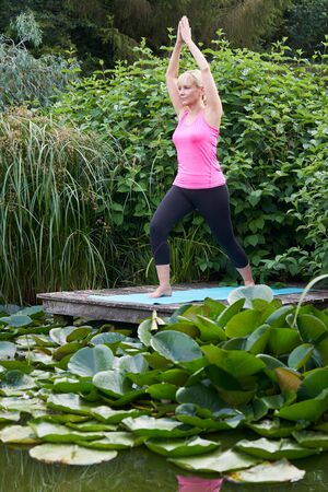 Mature Woman In Yoga Position On Wooden Jetty By Lake Stock Photo