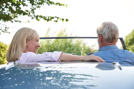 Rear View Of Mature Couple Enjoying Road Trip In Classic Open Top Sports Car Together