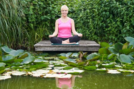Portrait Of Mature Woman In Yoga Position On Wooden Jetty By Lake