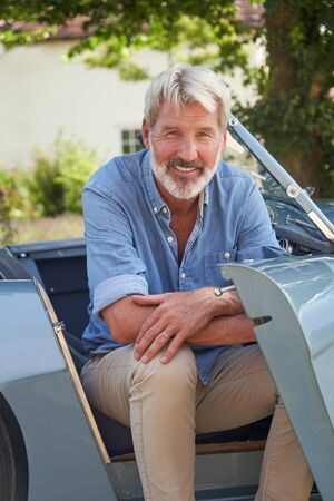 Portrait Of Proud Mature Man Sitting In Restored Classic Sports Car Outdoors At Home Stock Photo