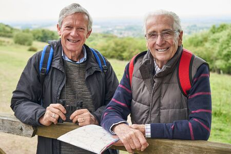 Portrait Of Two Retired Male Friends On Walking Holiday Resting On Gate With Map
