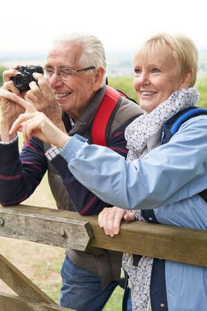 Senior Couple Hiking In Countryside Standing By Gate  And Taking Photo With Camera