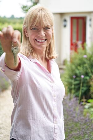 Portrait Of Mature Woman Standing In Garden In Front Of Dream Home In Countryside Holding Keys Stock Photo