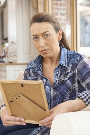 Unhappy Mature Woman Looking At Photograph In Frame Stock Photo
