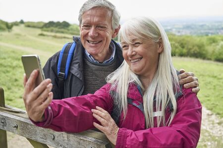 Smiling Senior Couple Hiking In Countryside Standing By Gate  And Taking Selfie On Mobile Phone