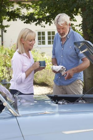 Mature Woman Bringing Hot Drink To Man Restoring Classic Sports Car Working On Engine Under Hood